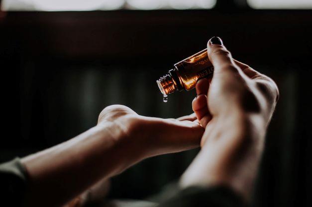 Une personne qui se verse de l'huile sur la main