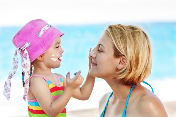 Maman met de la crème solaire à son enfant
