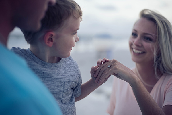 Un enfant regarde la bague de fiançailles de sa maman
