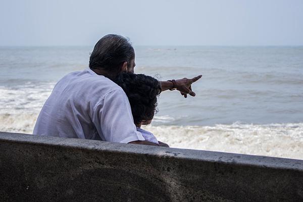 Grand-père avec son petit-enfant devant l'océan