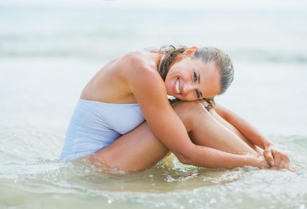 Jeune femme dans la mer en maillot de bain 1 pièce