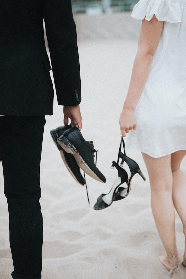 Couple de jeunes mariés pieds nus dans le sable