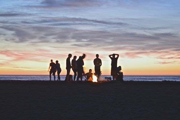 Vacances entre amis, un feu allumé sur la plage la nuit
